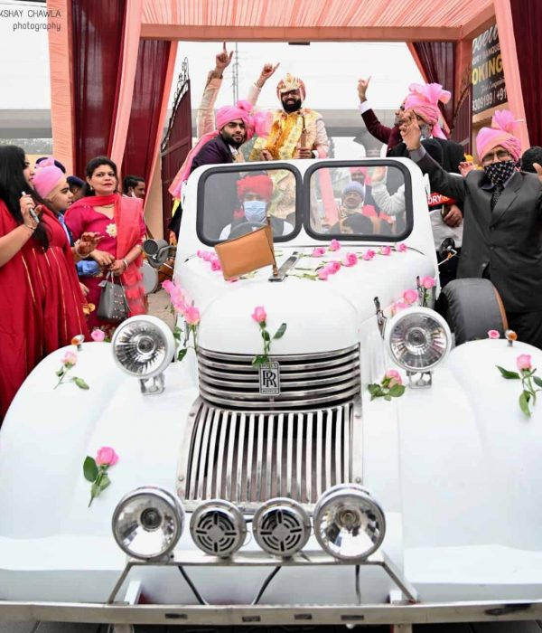 An indian guy going for his baaraat on white vintage car